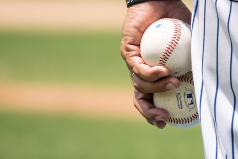 baseball player hand holding two balls