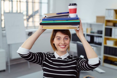 Woman holding stack of books on head.